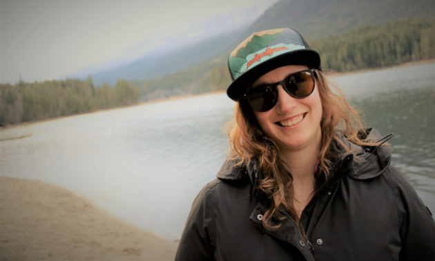 Karen Kornelsen wears a hat and sunglasses with a black coat in front of a blue lake in the woods.