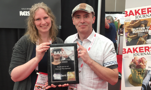 Michelle and Eric Forbes smile while holding their award for the prestigious Jake the Baker award from Bakers Journal magazine.