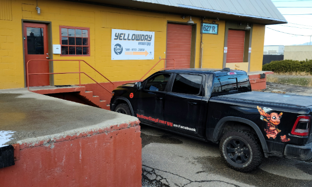 Yellowday Energy is a yellow building with an orange door. A black pickup truck with Yellowday Energy written on the side is parked in front.