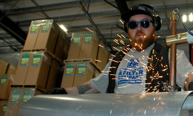 Kyle Grattan wears protective glasses and earmuffs as he works on a machine that sprays sparks.