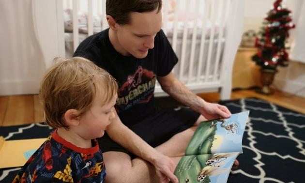 A father reads to his son on the floor.