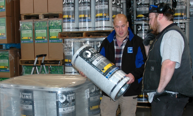 (L to R) Kyle Downey and Kyle Grattan, employees at Kootenay Filter Inc., look over products in their Nelson warehouse.