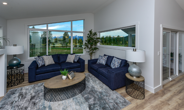 A living room with a grey carpet, blue couches, white walls and big windows.