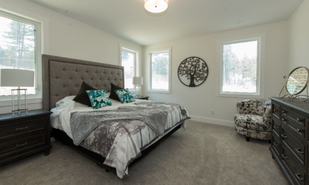 A bedroom with a grey floor, white walls and a white ceiling.