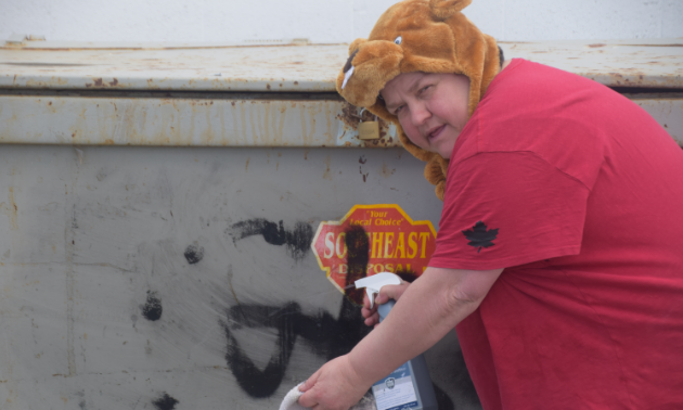 A woman wears a beaver hat costume and red shirt while rubbing off graffiti from a dumpster.