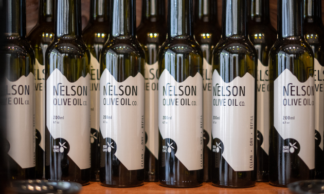 A line of dark green bottles with white Nelson Olive Oil labels on them.