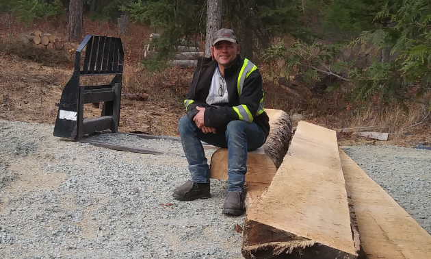 Darrin Brown sits on some cut up logs