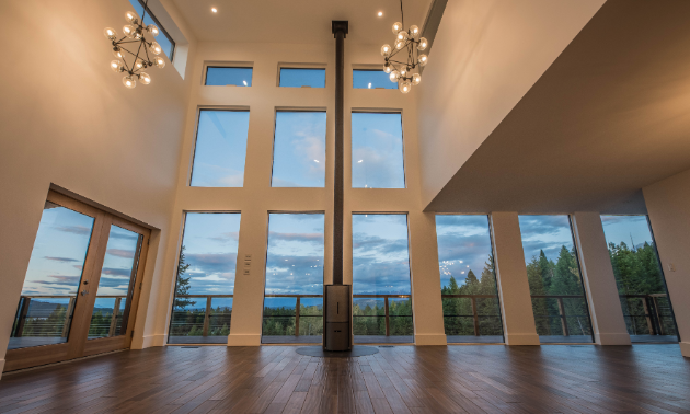 A tall, open living room with many large windows and chandeliers high above the wooden floorboards.