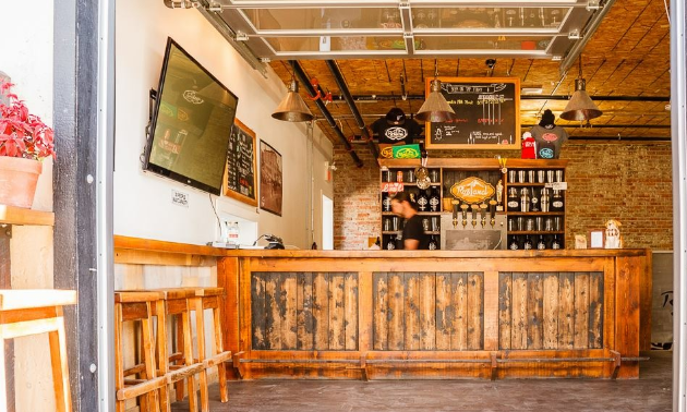 The taproom of Rossland Beer Company has a wooden bar with tan, wooden stools set to the side. A big widescreen TV hangs on the wall. Upside down cone lamps hang from the ceiling.