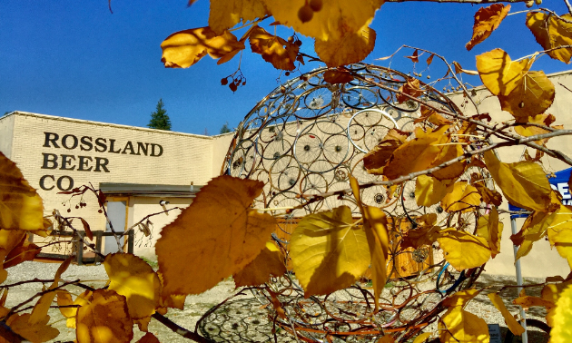 The front of Rossland Beer Company says the business' name in dark lettering on a beige building. In the foreground, yellow fall leaves are in front of a transparent, decorative golden sphere.