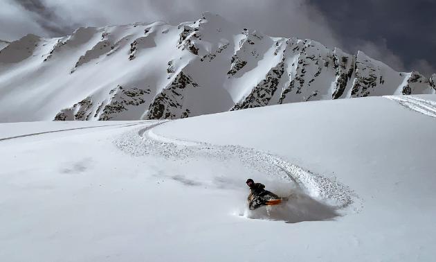 A snowmobiler shreds through fresh snow.