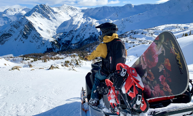 A snowmobiler looks off into the distant mountains. They have a red and black snowboard on their sled.