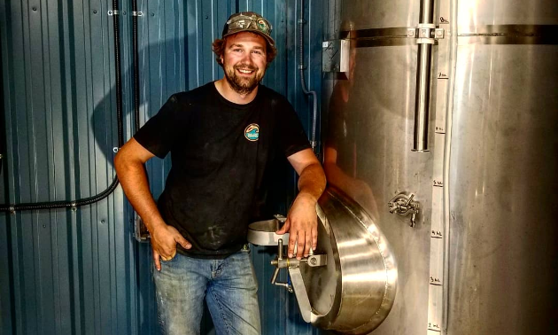 Hedin Nelson-Chorney, owner of Tailout Brewing, leaning against brewery tank.
