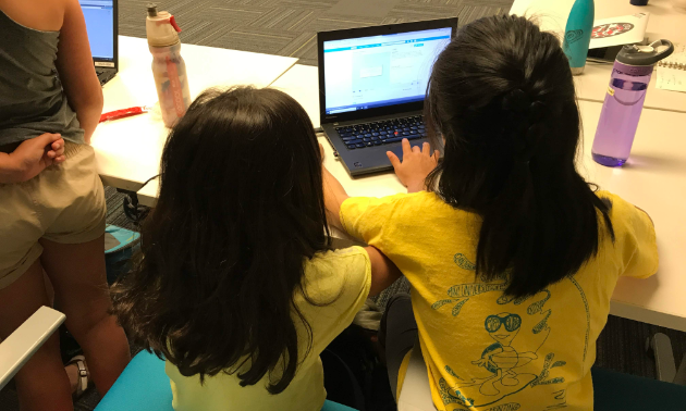 Two kids in yellow shirts interact with a computer.