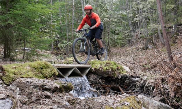 Jonathan Ladouceur, head of engineering, tests his printed bridge on one of the Kootenay Lake Village mountain bike trails.
