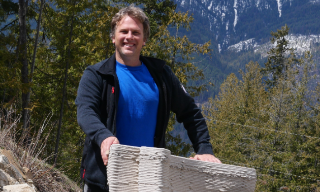 Ian Comishin smiles in front of a stack of printed concrete.