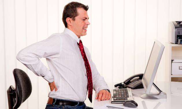 A man grabs at his back in pain while sitting at a desk