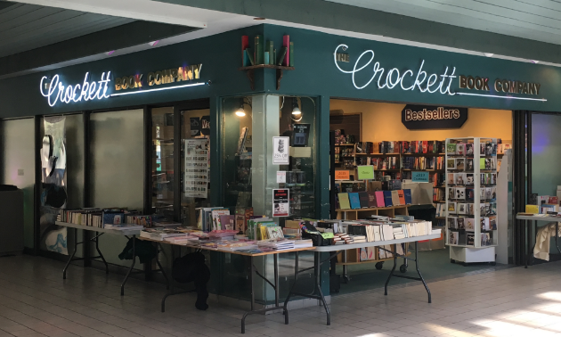The Crockett Book Co. is a bookstore with a couple of display tables and stands in front of the store.