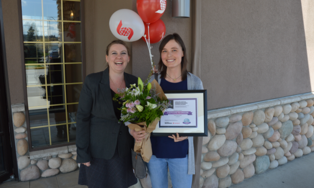(L to R) Amie Lubbers, sales co-ordinator for Kootenay Business magazine, presents one of three Influential Women In Business awards to Stephanie McGregor, owner of The Paw Shop in Cranbrook.