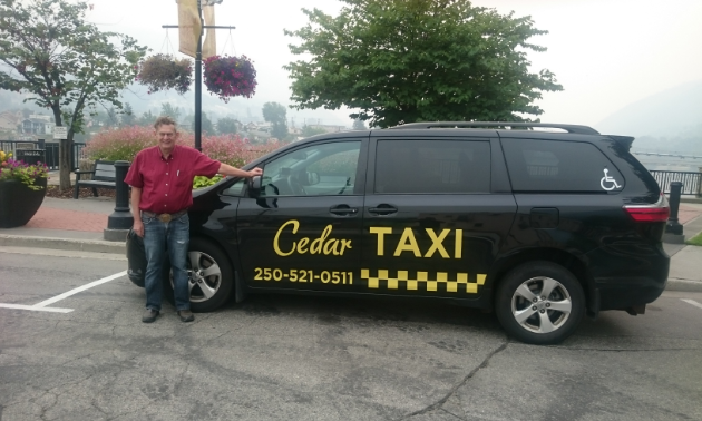 Ian Thomas stands next to his Cedar Taxi van