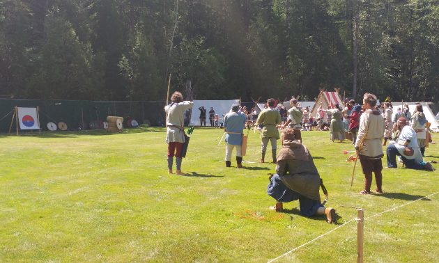 Archers shoot arrows at targets.