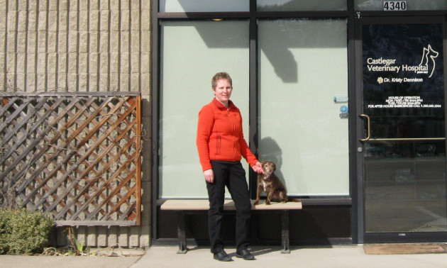 Dr. Kristy Dennison stands in front of Castlegar Veterinary Hospital with a dog.