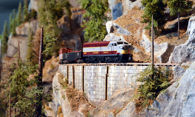 A toy train car rides along a track.