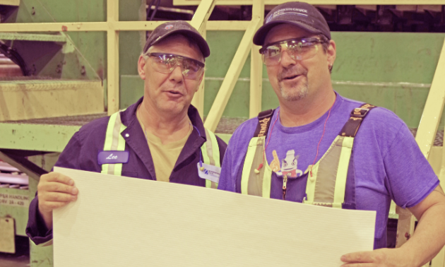 (L to R) Lee Spence and Wilf Davis, employees of Skookumchuck Pulp Inc., hold a sheet of high-quality Northern Bleached Softwood Kraft (NBSK) pulp. These sheets of pulp, measuring 86 centimetres by 74 centimetres, are stacked together to produce bales of pulp. Each bale weighs approximately 245 kilograms.