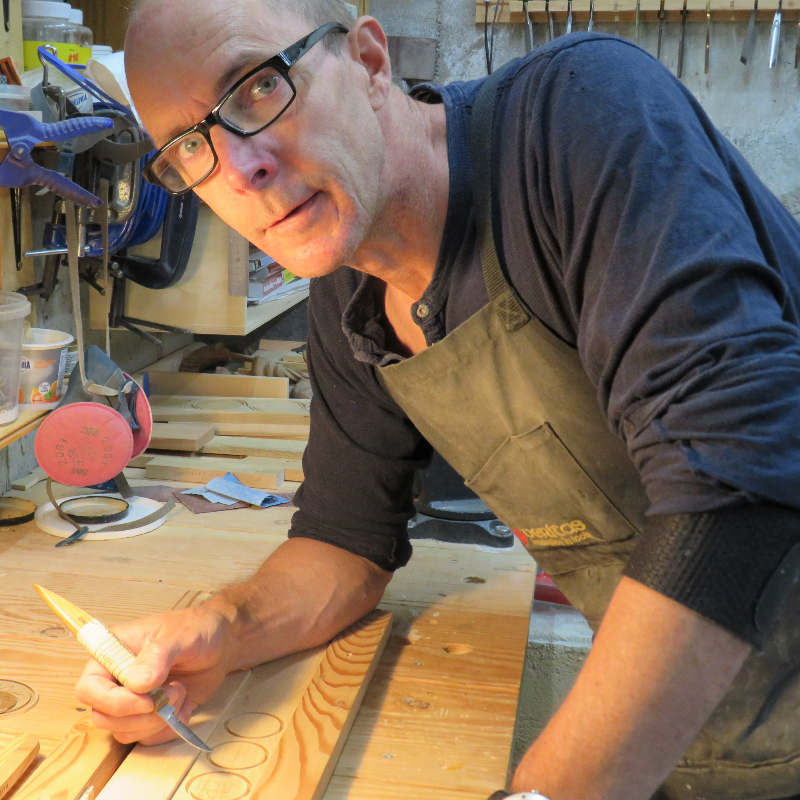 Charmain Bibby smiles, wearing glasses and a blue shirt with red flowers. Mike Bibby carves into a piece of wood on a work bench.