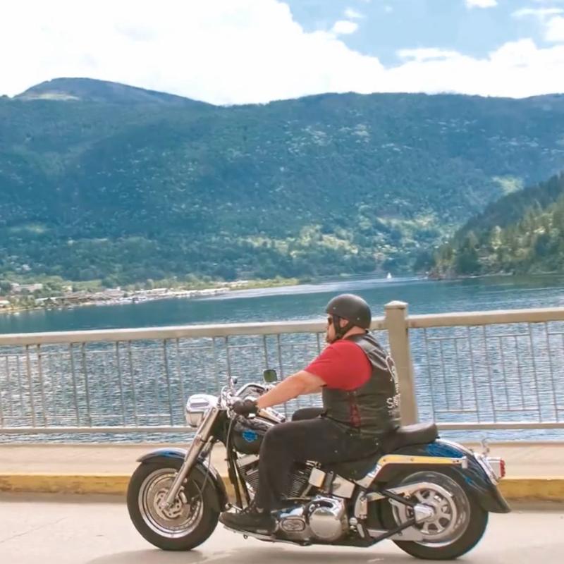 Brad Pommen rides a Harley-Davidson Fat Boy motorcycle over an orange bridge in Nelson, B.C.