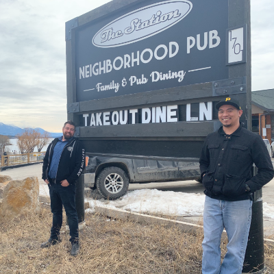 """Chris Policar and Ryan """"Butter"""" Karl stand in front of a sign that reads The Station Pub."""