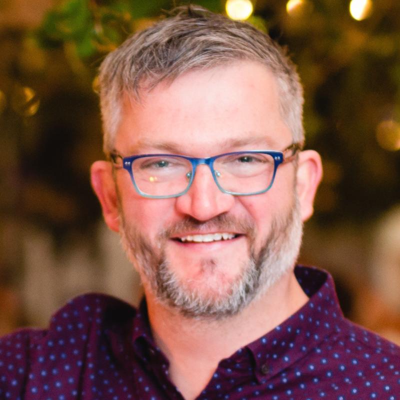 Daniel Holden smiles, wearing black-rimmed glasses and a salt and pepper beard.