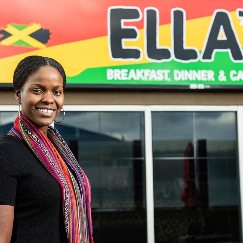 Aleitha Harvey smiles in front of her sign for her restaurant, Ella's.