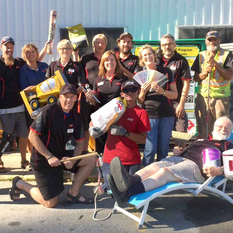 Jeff Davie (up front in the middle with a black hat), his wife, Monica Davie (behind Jeff, wearing a blue shirt), and the team at Kaslo Building Supplies pose for a group photo.