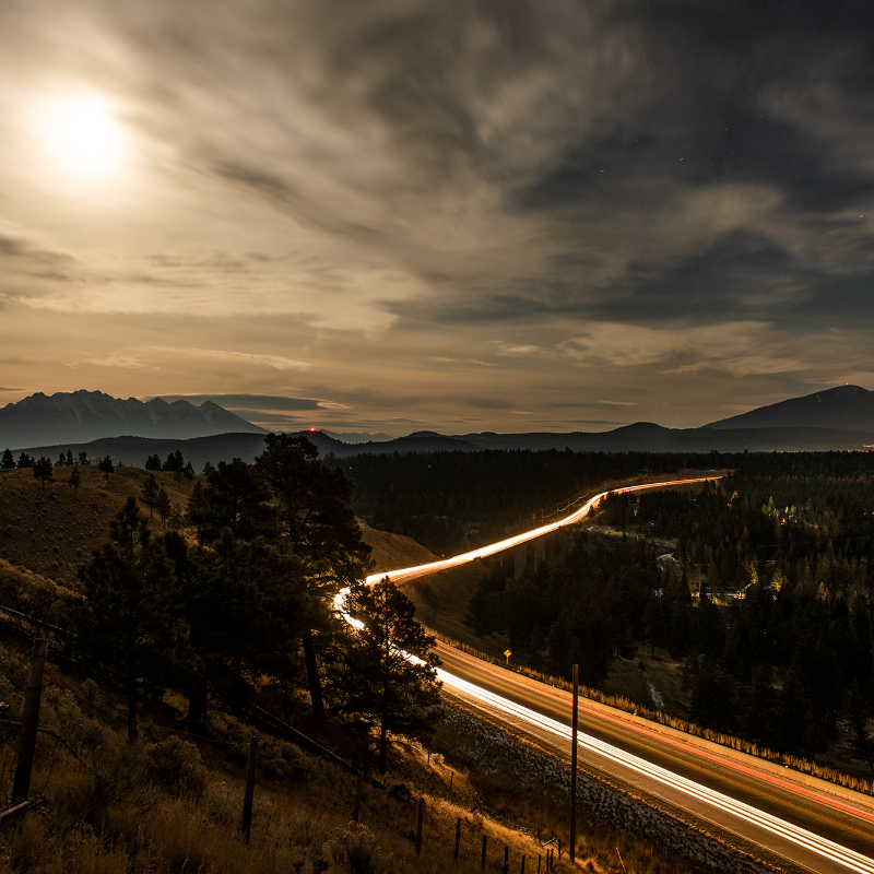 The mountains surrounding Cranbrook and the Cranbrook-Kimberley highway with streaks of light zooming across it.