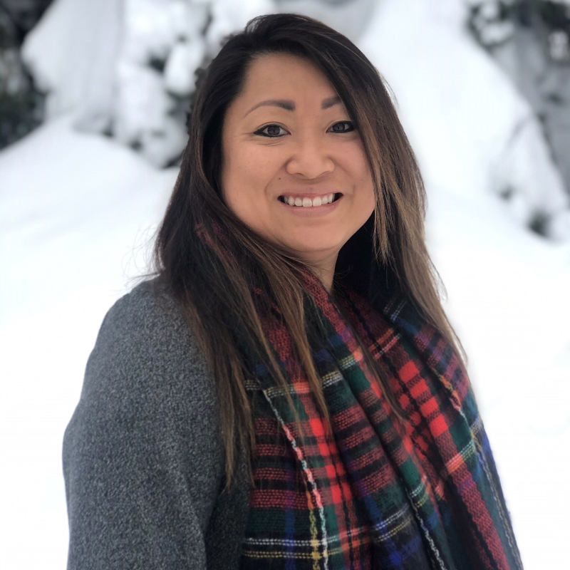 Stacey Brensrud has long brown hair and wears a grey shirt and red scarf. She smiles in the photo. Snowy trees are in the background.