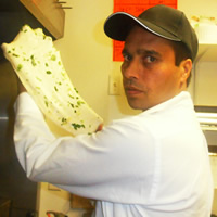 Man wearing a baseball cap and chef's whites with a flatbread-type sheet of dough in his hands