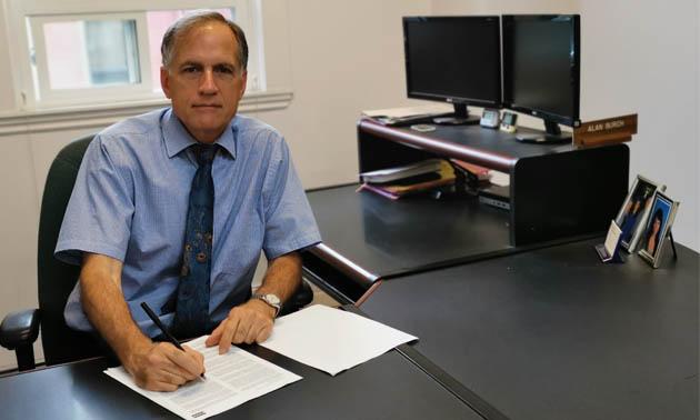 Attorney Alan Burch sitting at his desk.