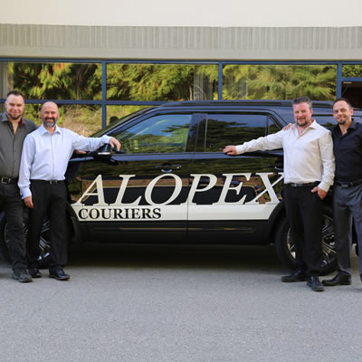 Four staff of Alopex Couriers stand in front of one of their fleet vehicles, a black car with the company's name in white letters on the side of the car.