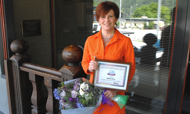 Amber Hayes stands holding a bouquet and her Influential Women in Business award certificate.