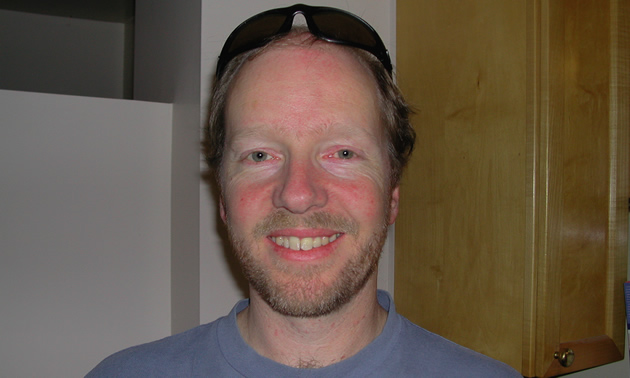 Andrew Cowan has blond hair, a light beard and sunglasses on top of his head. He's wearing a blue t-shirt.