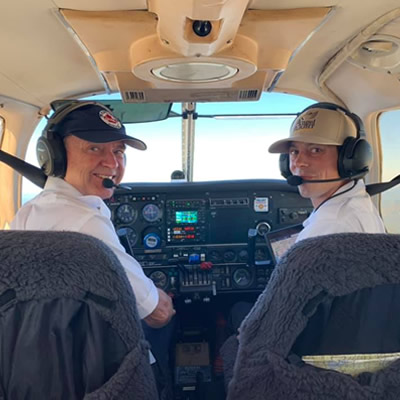 Two pilots in cockpit of small plane.
