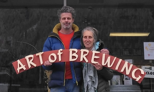Owners Breg and Maarten Lammers are holding a sign that says Art of Brewing, the name of their store.