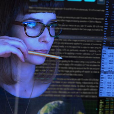 Graphic showing woman holding pencil looking at computer screens.