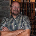 Bob Johnson, wearing a plaid shirt stands in front of an iron work gate leading to a wine cellar.