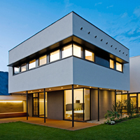 A graphic passive solar home rises attractively into the sky. It is white and features walls of windows.