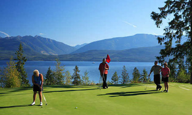 Two people teeing off on lakeside course.