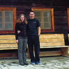 young couple standing in front of a large rustic wooden building
