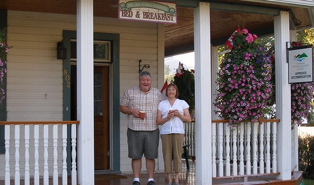 Jo Anne and Patrick Burke standing on the veranda of their Bed and Breakfast, the Old Nurses Residence, in Fernie B.C.