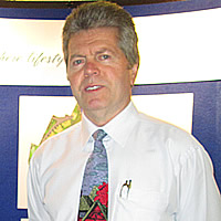 Gray-haired man in white shirt and tie stands in front of a curved photo display